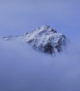 Mountain peak glimpsed through the clouds.