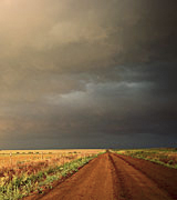 Photo of a road leading through fields to a gray sky in the distance.