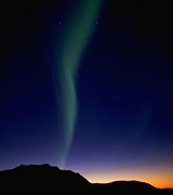 Aurora borealis against an indigo sky above dark hills.