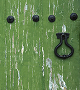 Old green wooden door with a black handle.