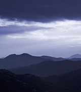 Misty hills beneath dark clouds at dusk.