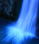 Photo of a high waterfall with blurred white spray against a blue background.
