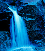 Blue waterfall on dark rocks.