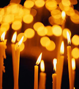 Slender lit candles, with those in back blurred like golden coins.