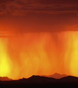 Photo of orange rain streaming from red clouds against a yellow sky over dark hills.