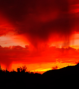 Rain streaming from red clouds over the desert at sunset.