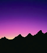 Photo of black mountain peaks in silhouette against a pink and indigo sunrise.