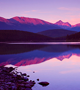 Mountains reflected in a still lake at sunrise.