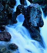 Icy blue mountain waterfall flowing over rocks.
