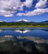 A distant snow-capped mountain reflected in a calm lake.