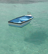 Rowboat floating in clear green waters.